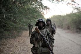 A handout photo released by the African Union-United Nations Information Support team shows Ugandan soldiers of the African Union Mission in Somalia take a break as they march toward the town of Qoryooley, Somalia, on March 22, 2014 (AU UN IST Photo/AFP, Tobin Jones)