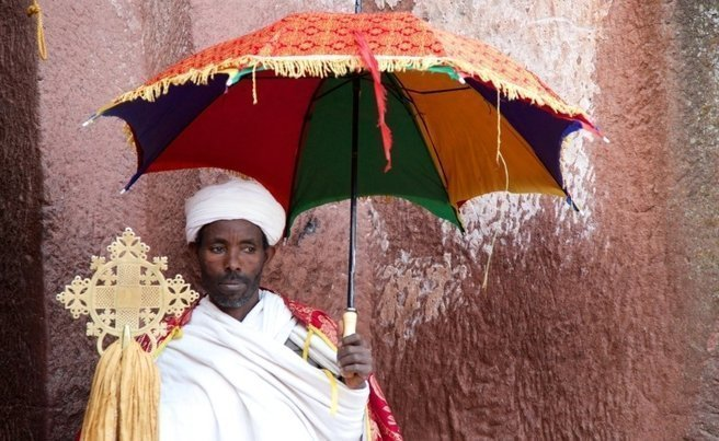 A priest holds an umbrella at a rock-hewn church in Lalibela. Picture: Stephen Scourfield
