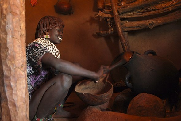 A woman in the Omo Valley prepares coffee using tools made from gourds (Photograph by Sarah Erdman)