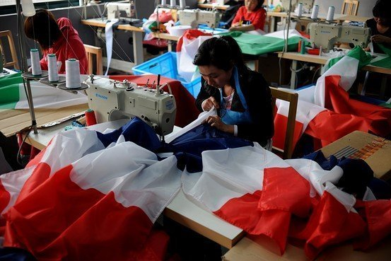 Workers at a factory in Hangzhou, China, making national flags for the 2014 FIFA World Cup.     Agence France-Presse/Getty Images