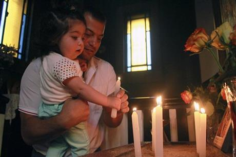 In this Sunday June 1, 2014 photo, Armen Madatyan and his 1 year-old daughter Stella light a candle at the church in Addis Ababa, Ethiopia. There is a small handful of people keeping the Armenian community in Ethiopia alive. Despite a fall in numbers from a peak of 1,200 in the 1960s to less than 100 people today, the Armenian school, church and social club still open their doors. (AP Photo/Elias Asmare)