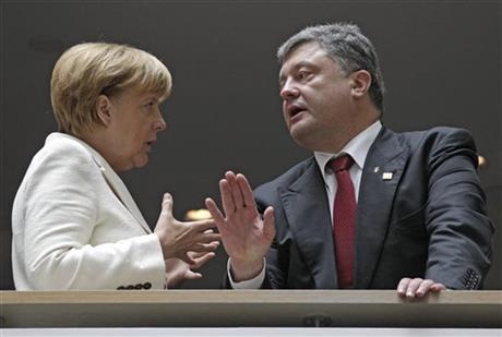 Ukrainian President Petro Poroshenko, right, talks with German Chancellor Angela Merkel during an European People's Party summit ahead of the EU summit in Brussels, Saturday, Aug. 30, 2014. EU leaders, in a one day summit, are set to decide who will get the prestigious job as the 28-nation bloc's foreign policy chief for the next five years. They will also discuss the current situation in Ukraine. (AP Photo/Yves Logghe)