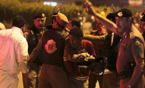 In this November 9, 2013 file photo shows members of Saudi security forces detain Ethiopian workers during a riot in Manfouha, southern Riyadh. (Reuters)