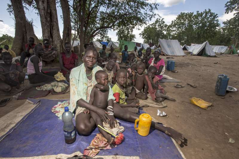 South Sudanese refugees sit in the shade of a tree. They are living in makeshift shelters as they wait for UNHCT tents. Ethiopia hosts more than 600,000 refugees.