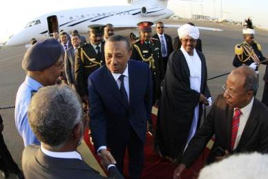 The Libyan prime minister shakes hands with Sudanese foreign minister Ali Karti after his arrival to Khartoum on 27 October 2014 (Photo: AFP/Ashraf Shazly)