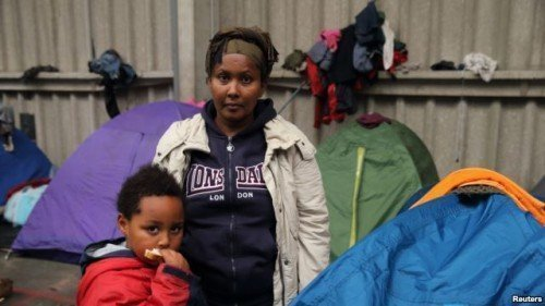 FILE - Tsega, 38, a migrant who fled Eritrea six years ago, poses with her son Naher, 5, in front of their tent at a migrant shelter in Calais, northern France, October 2014.
