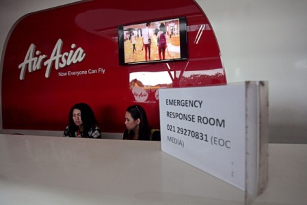 Missing plane: Two staff members of AirAsia Indonesia stand by at an information post at Terminal 3 of Soekarno-Hatta International Airport, on Sunday. AirAsia has opened information posts for the families of passengers and crew members aboard flight QZ8501 which lost contact with air traffic control while en route from Surabaya, East Java, to Singapore, on Sunday. (JP/AWO)