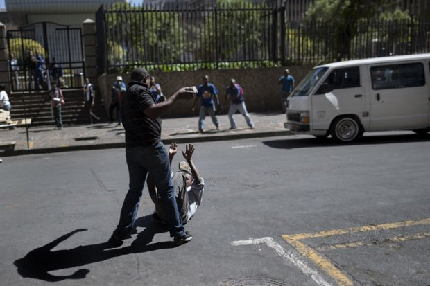 A local taxi driver pelts a foreigner with stones during a street brawl in Johannesburg on April 15, 2015 (AFP Photo / Marco Longari)