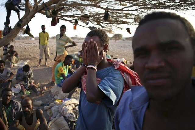 A man from Ethiopia covers his face as he waits with other illegal immigrants for a boat to cross into Yemen outside the town of Obock, in north Djibouti. Goran Tomasevic / Reuters / February 22, 2015