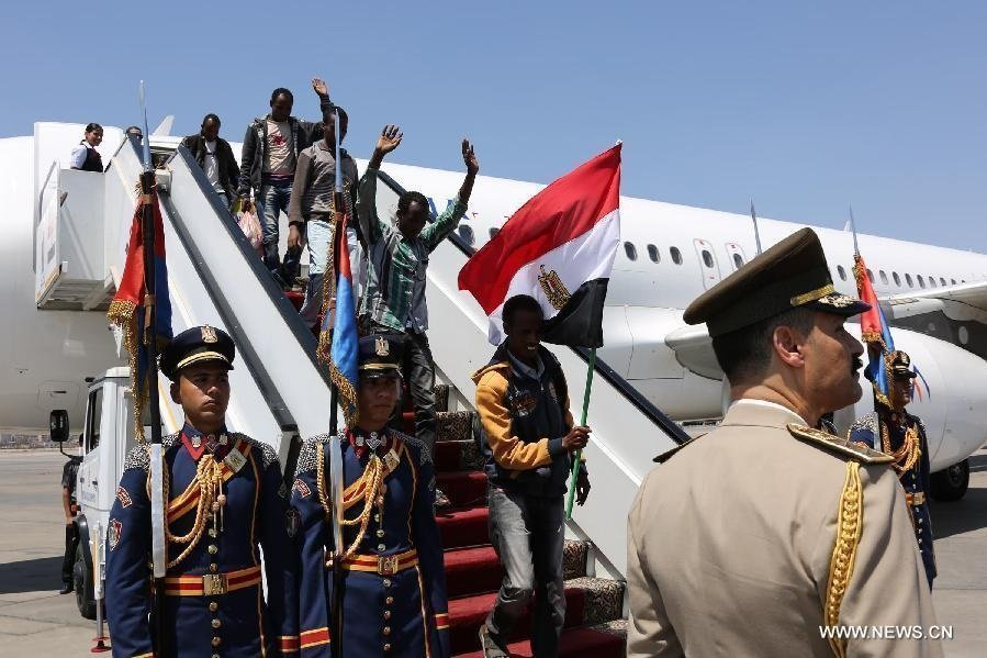 Ethiopians holding an Egyptian national flag walk down from a plane at the Cairo International Airport in Cairo, Egypt, on May 7, 2015. A group of Ethiopians freed from Islamic militant kidnappers in Libya arrived in Cairo Thursday, state-run Nile TV reported. (Xinhua/MENA)