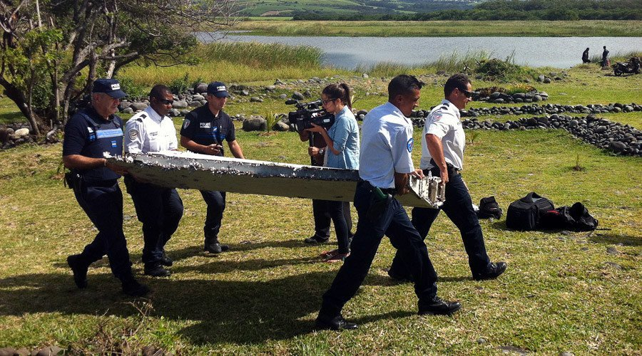 Police carry a piece of debris from an unidentified aircraft found in the coastal area of Saint-Andre de la Reunion, in the east of the French Indian Ocean island of La Reunion, on July 29, 2015. © Yannick Pitou / AFP via RT