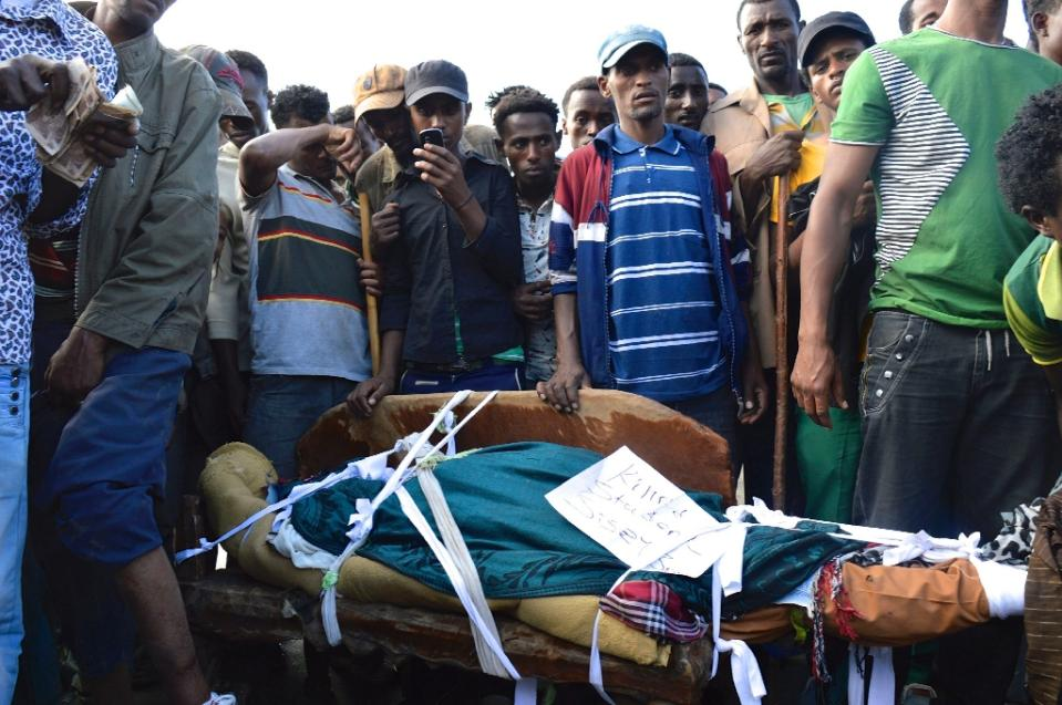 People in Wolenkomi in Ethiopia near the body of a protestor  - AFP Photo - via Yahoo