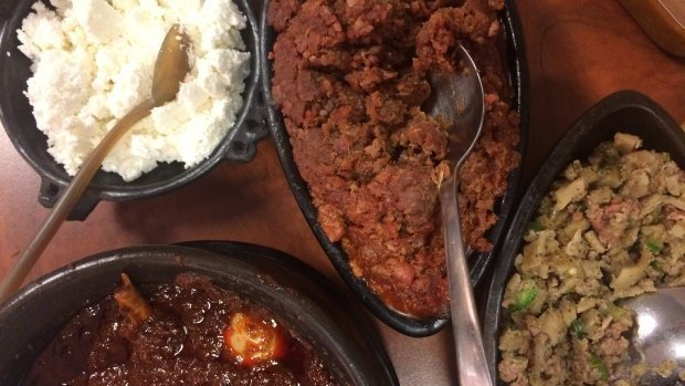 A dish often prepared at Ethiopian Orthodox Christmas, kitfo (centre, top) is a flavourful minced beef dish that's cooked with clarified butter and seasoned with cayenne pepper, cardamon, and salt. / CBC Photo